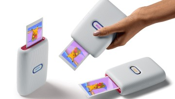 The instax mini Link SE film printer in various positions printing a picture of a Pikachu