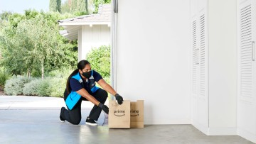 An Amazon shopping specialist leaves a grocery package at a garage