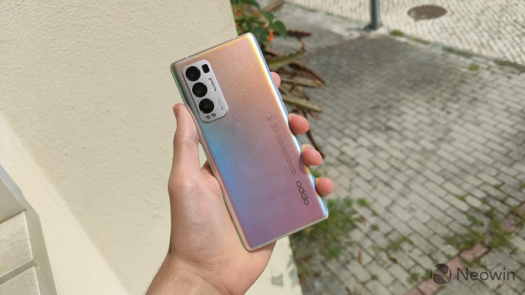 OPPO Find X3 Neo held in hand with the back facing the camera in front of a wall