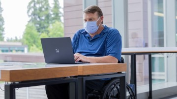 A man sits on his wheelchair while looking at his laptop screen