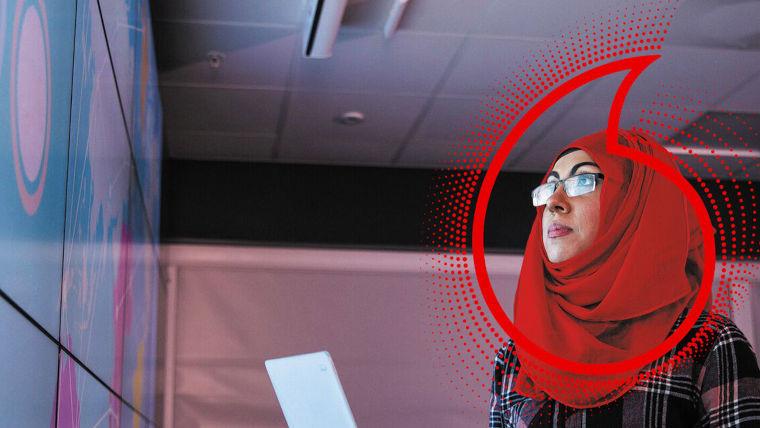 A woman looking at a monitor and a Vodafone logo