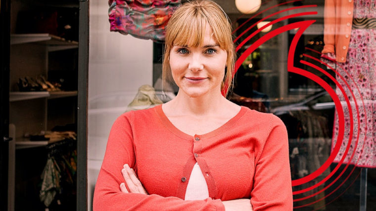 A woman with the Vodafone logo in the background