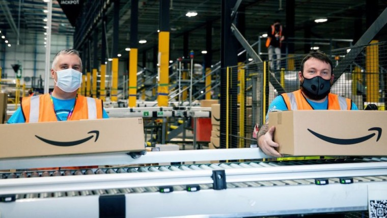 Amazon workers preparing delivery boxes inside a warehouse