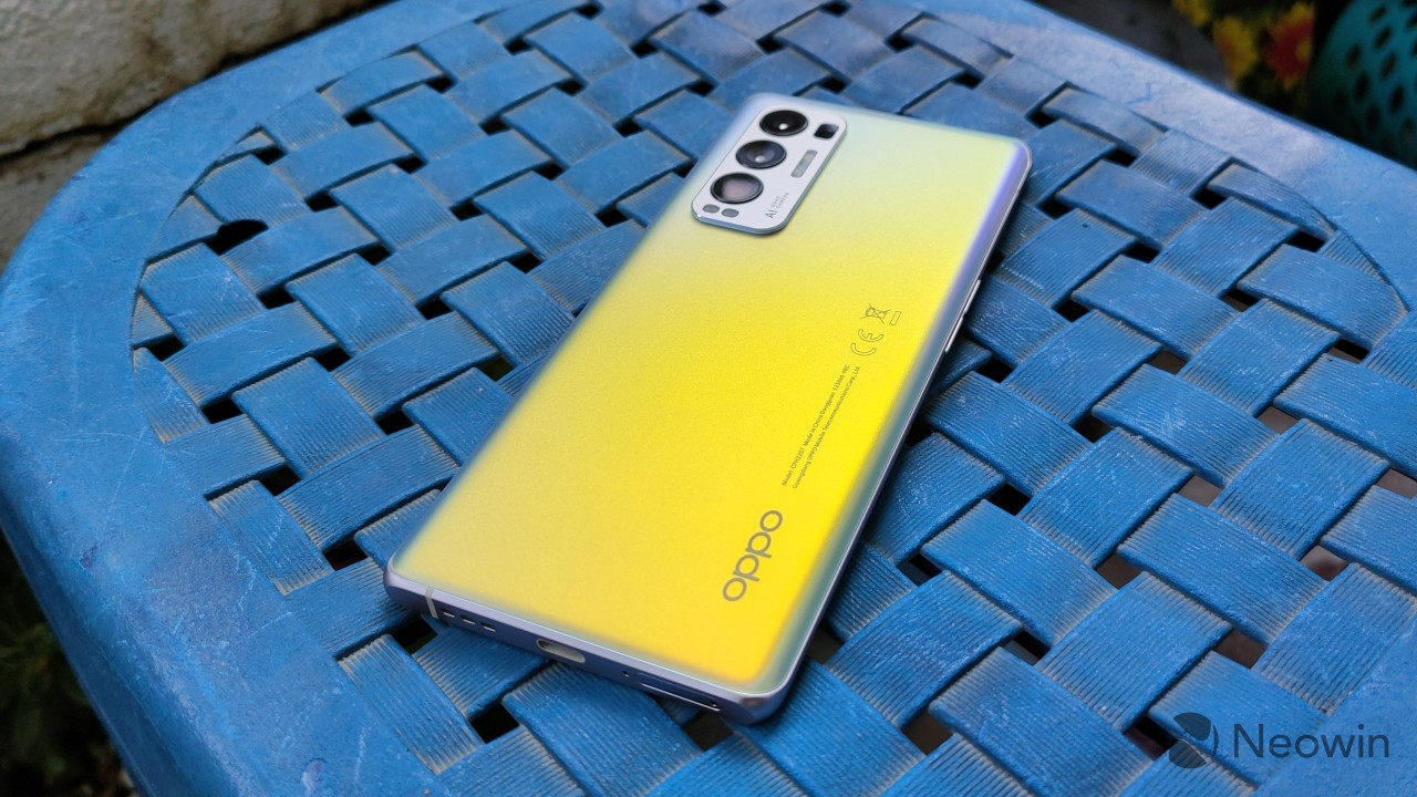 Angled overhead view of the back of the OPPO Find X3 Neo reflecting yellow light