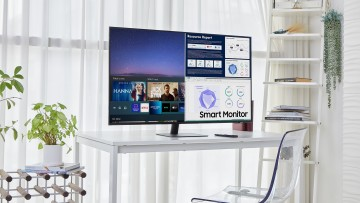 A 43 inch Samsung Smart Monitor and its remote on a white desk in an office
