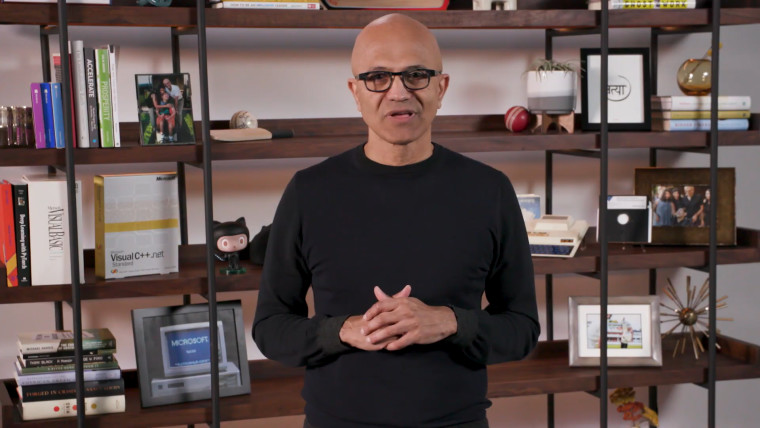Microsoft CEO Satya Nadella standing in front of a shelf with many things