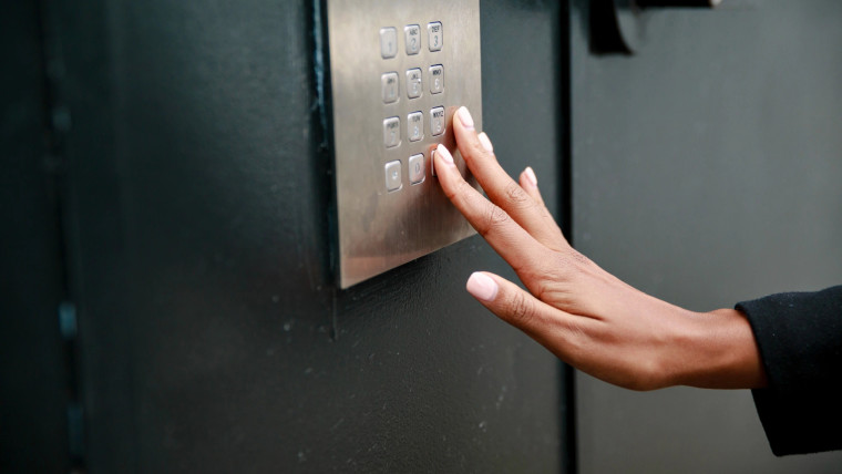 Airbnb hand touching buttons on a keypad