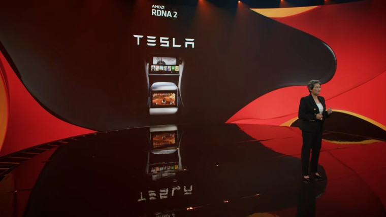 AMD CEO Lisa Su stands in front of a display showing a Tesla in-car system with multiple games avail
