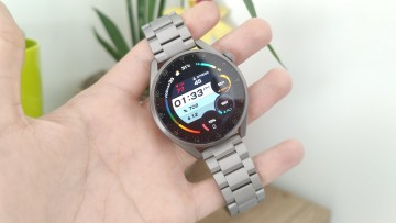 Huawei Watch 3 Pro resting on a hand and displaying a detailed watch face