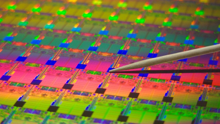A toothpick pointing towards dies on a silicon chip wafer