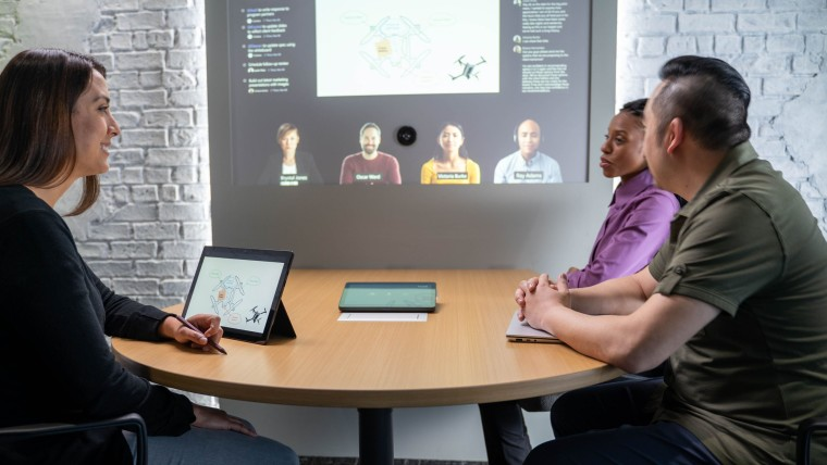 People sitting at a table with a tablet in front and a Teams call with four people on a projector