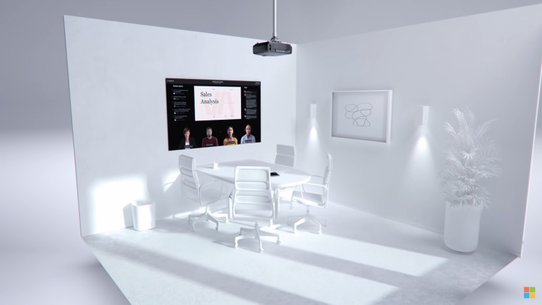 A white room with a table and chairs with a large display showing a Teams call