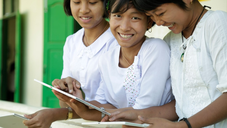 Three children looking at tablets