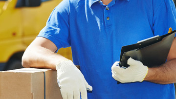 amazon worker leaning on box with white gloves on