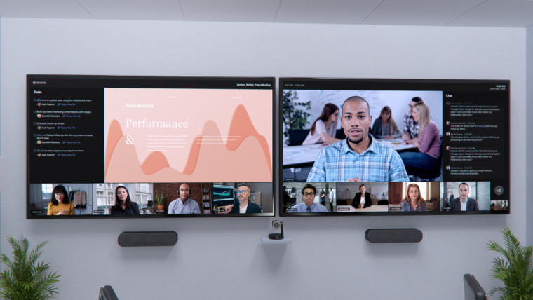 Two large screens running a Teams meeting with multiple video feeds shown across both of them