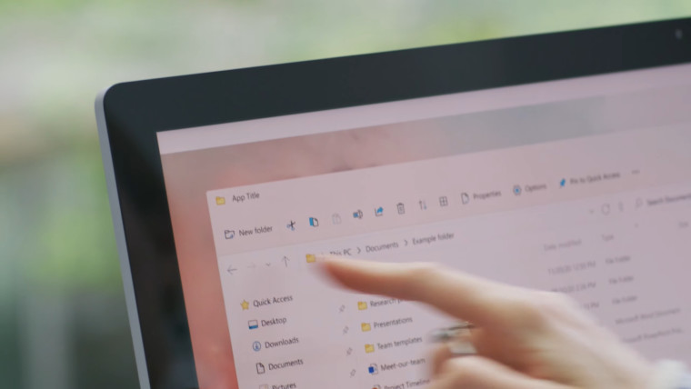 A woman pointing to a screen that contains some files on Windows 11 File Explorer