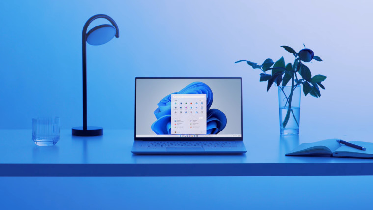 A laptop running Windows 11 placed in a fancy studio lit in blue