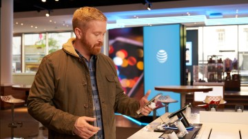 A customer holding a phone inside an AT&T store