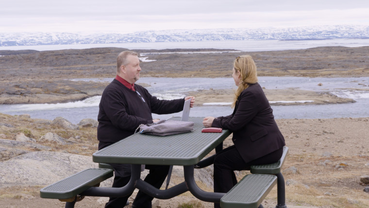 Two people sitting at a table with the laptop on and a picturesque background