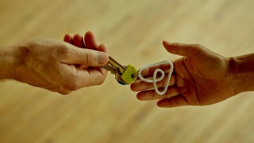 A hand handing a key to another hand