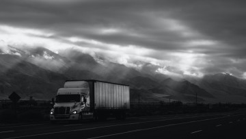 A truck travelling on a very cloudy day