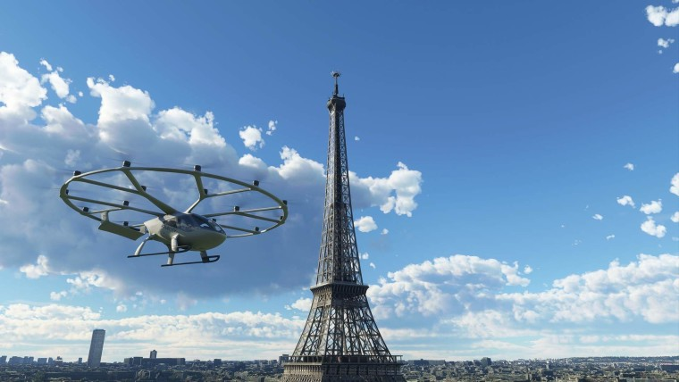 A white Volococity helicopter with multiple blades at the top flying next to the Eifel Tower