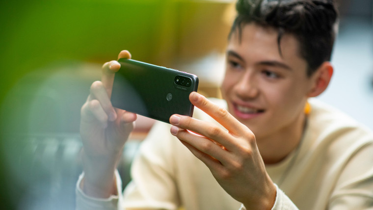 A man taking a picture with the Moto E20